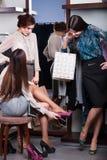Vänner hjälper att välja en anslå skor Arkivbild