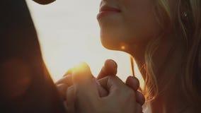 Vänner i ett fält på solnedgången Flicka- och grabbinnehavhänder lyckligt le för par arkivfilmer