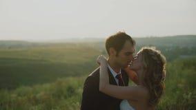 Vänner i ett fält på solnedgången Flickan kramar grabben lyckligt le för par lager videofilmer