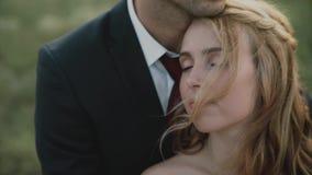 Vänner i ett fält på solnedgången Grabben kramar flickan lyckligt le för par stock video