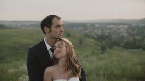 Vänner i ett fält på solnedgången Grabben kramar flickan lyckligt le för par lager videofilmer