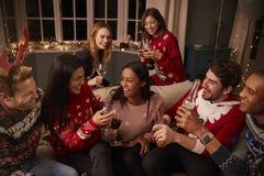 Vänner i festliga förkläden firar på julpartiet royaltyfri bild
