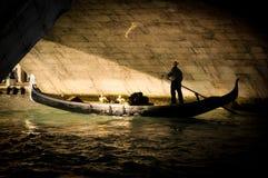 Vänner i gondol under en bro i Venedig royaltyfri foto