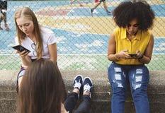 Vänner i parkera genom att använda smartphones royaltyfri bild