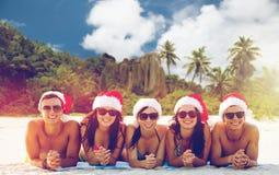 Vänner i santa hattar på stranden på jul royaltyfri foto