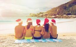 Vänner i santa hattar på stranden på jul arkivfoto