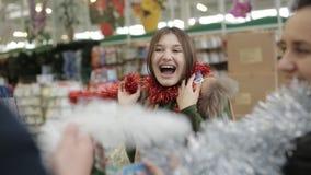 Vänner i supermarket på julförsäljningen väljer färgrikt glitter för att dekorera julgranen lager videofilmer