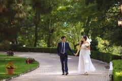 Vänner lyckligt och promenerar lyckligt gränden i ett grönt tätt parkerar, meddelar och skrattar på deras bröllopdag royaltyfri foto