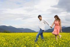 Vänner man, och kvinnan går på blommafältet Royaltyfria Bilder