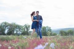Vänner man, och kvinnan går på fält med röda blommor Royaltyfria Bilder