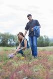 Vänner man, och kvinnan går på fält med röda blommor Arkivfoto