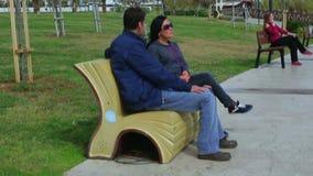 Vänner man och kvinnan som talar, medan sitta på en parkerabänk stock video