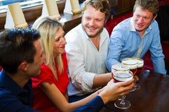 Vänner med öl i en bar Arkivbild