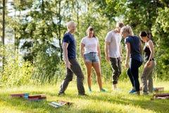 Vänner med byggnadskvarter på gräs- fält i skog royaltyfri foto