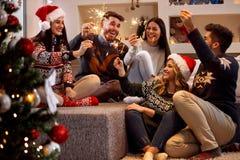 Vänner med gnistrandet som firar juldag Royaltyfri Fotografi