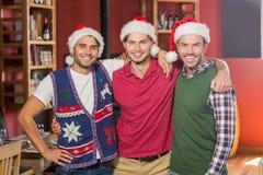 Vänner med julhattar som ler på kameran Royaltyfria Bilder