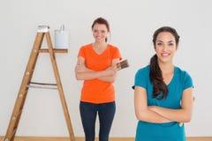 Vänner med målarfärgborstar och stege i ett nytt hus fotografering för bildbyråer