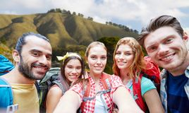Vänner med ryggsäcken som tar selfie över stor sur arkivfoto