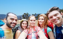 Vänner med ryggsäcken som tar selfie över stranden arkivfoton