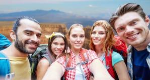 Vänner med ryggsäcken som tar selfie i trä royaltyfria foton