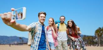 Vänner med ryggsäcken som tar selfie vid smartphonen arkivbilder