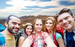 Vänner med ryggsäcken som tar selfieoveberg arkivfoto