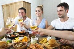 Vänner med vitt vin som rostar över den tjänade som tabellen med mat Royaltyfri Fotografi
