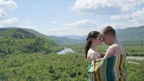 Vänner Naket omfamna för par som täckas av filten Grabben omfamnar flickan på grön bergbakgrund arkivbild
