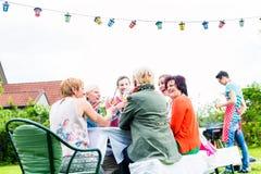 Vänner och grannar på den långa tabellen som firar partiet arkivbilder