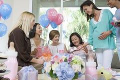 Vänner och gravid kvinna på en baby shower Royaltyfri Bild