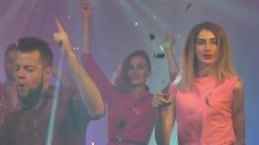 Vänner på dansen av en nattklubb med fallande konfettier Röka färgrik bakgrund långsam rörelse stock video