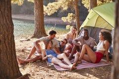 Vänner på en campa tur som kopplar av på en filt vid en sjö arkivbild