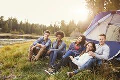 Vänner på en campa tur som kopplar av vid ett tält, ser till kameran Arkivbilder