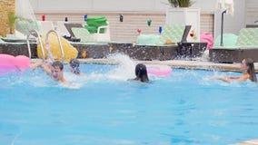 Vänner på en sommarpartiungdom har gyckel i blått vatten och gör färgstänk in i simbassäng