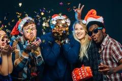 Vänner på ` s för det nya året festar och att bära santa hattar, dansen och blåsa konfettier royaltyfria foton