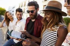 Vänner på semester i Ibiza som ser upp en resehandbok, slut fotografering för bildbyråer