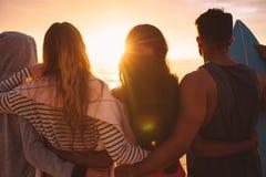 Vänner på semestern som står på stranden royaltyfria foton