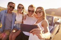 Vänner på vägturen Sit On Convertible Car Taking Selfie Royaltyfri Fotografi