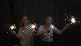 Vänner pojke och flicka med tomtebloss i händer som har roligt och kyssande långsam rörelse arkivfilmer