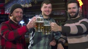 Vänner poserar med exponeringsglas av öl på baren arkivfoton