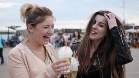 Vänner rostar, två kvinnliga leenden och att se kameran som har drinkar, flickvänner med kylde coctailar i hand arkivfilmer