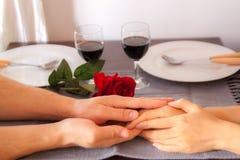 Vänner sitter på en tabell, på tabellen en röd ros, ett exponeringsglas av vin och vita plattor Händer av vänner på tabellen, när arkivbild