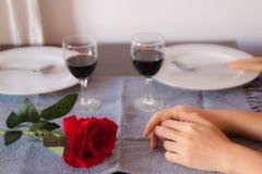 Vänner sitter på en tabell, på tabellen en röd ros, ett exponeringsglas av vin och vita plattor Händer av vänner på tabellen, när royaltyfria bilder