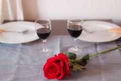 Vänner sitter på en tabell, på tabellen en röd ros, ett exponeringsglas av vin och vita plattor Händer av vänner på tabellen, när arkivbilder
