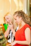Vänner skor shopping i en galleria Royaltyfria Bilder