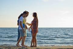 Vänner som är roliga på stranden under solnedgångsolljus arkivbilder