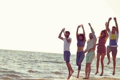 Vänner som är roliga på stranden under solnedgångsolljus royaltyfria foton