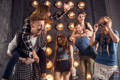Vänner som är roliga på studioväggen med lampor Royaltyfri Foto