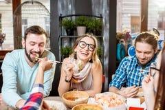 Vänner som äter asiatiska mål på restaurangen Royaltyfri Bild