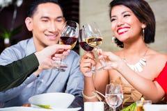 Vänner som äter middag i utsmyckad restaurang Arkivfoton